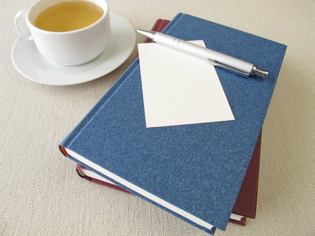 reading material: Books, blank sheet of paper and cup of tea Stock Photo