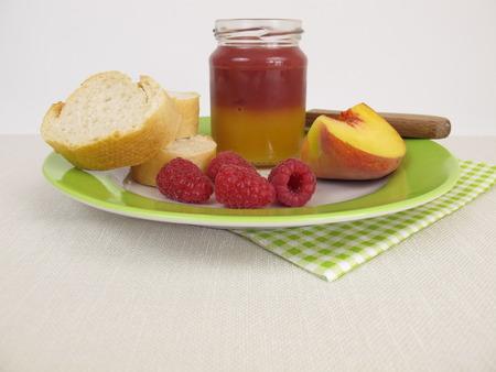 melba: Desayuno con el melocotón bicolor y mermelada de frambuesa Foto de archivo