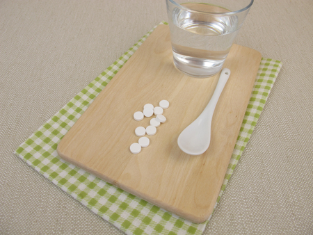 salts: Schuessler salts tablets and glass of water Stock Photo