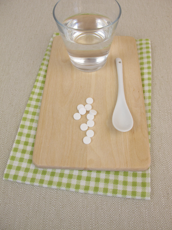 SELF HEALING: Schuessler salts tablets and glass of water Stock Photo