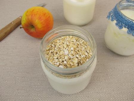 avena en hojuelas: Yogur en tarros de yogur con fabricante de copos de avena Foto de archivo