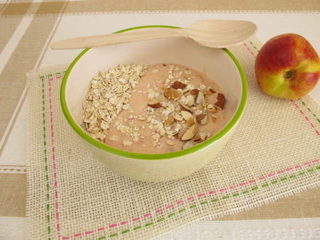 avena en hojuelas: Smoothie bowl with rolled oats, nectarines and hazelnuts Foto de archivo
