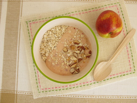 rolled oats: Smoothie bowl with rolled oats, nectarines and hazelnuts Foto de archivo