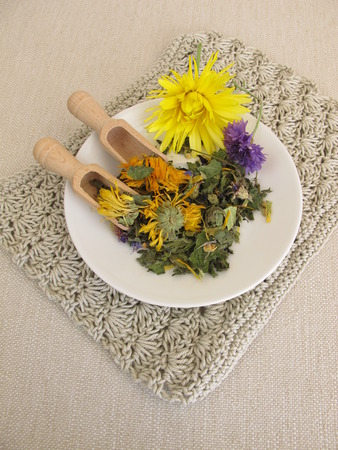 Herbal tea mix with flowers on a small plate