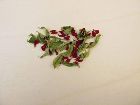 Dried pomegranate leaves and dried pomegranate flower on a wooden board