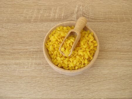 Pure beeswax pastilles in a wooden bowl for natural cosmetics, candles or beeswraps Stock Photo