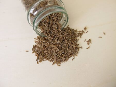 Caraway seeds, Carum carvi, on a wooden board Stock Photo