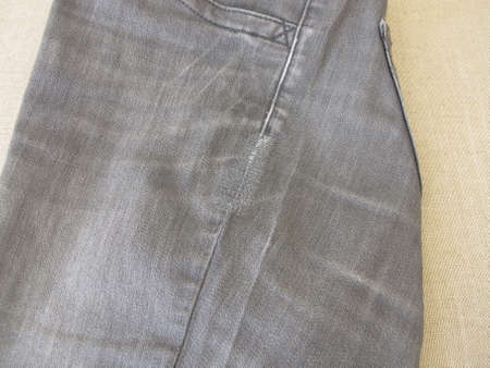 Repair garments, stitched seams on a worn jeans trousers with the sewing machine