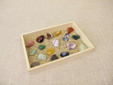 Tumbled gemstones in a wooden box with sand Archivio Fotografico