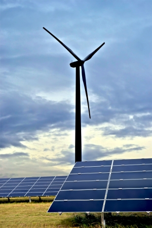 electricity tariff: one wind turbine and solar panels in a field