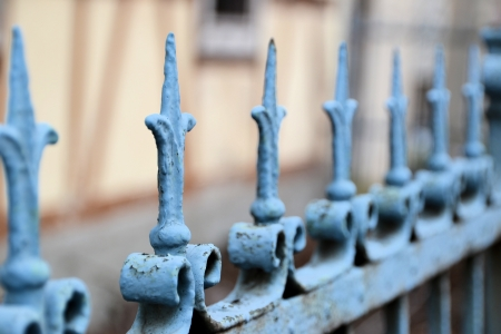 insurmountable: an old metal fence in front of a house