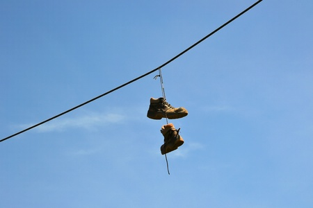 unreachable: Hanging shoes on a power cable in Magdeburg Stock Photo