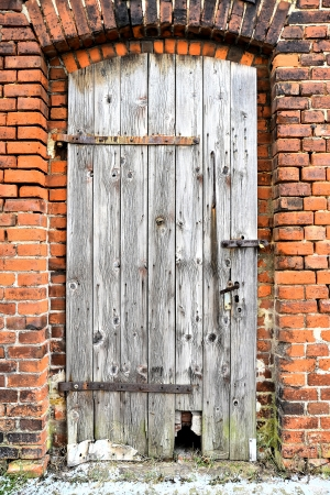 company premises: old wooden door of an industrial building Stock Photo