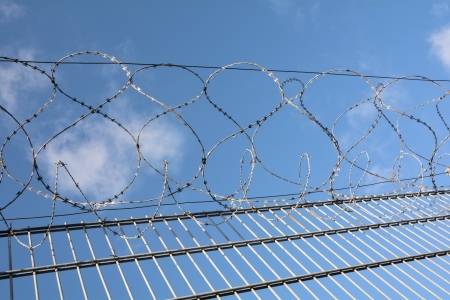 land locked: a high fence with barbed wire Stock Photo