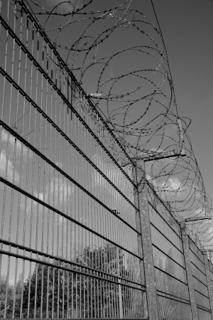 pointedly: a high fence with barbed wire Stock Photo