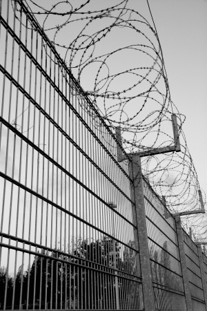 a high fence with barbed wire Stock Photo