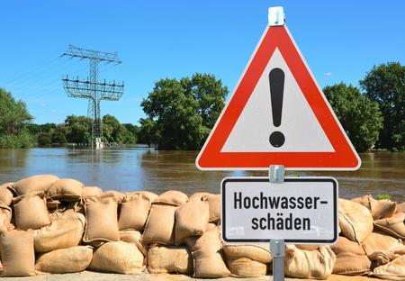zandzakken en een waarschuwingsbord op de oevers van de rivier de Elbe tijdens de vloed in Magdeburg Stockfoto