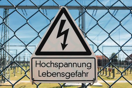warning sign on the fence of a substation photo