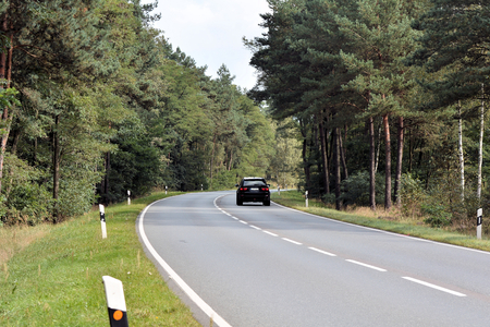 high stakes: car on a country road through a forest