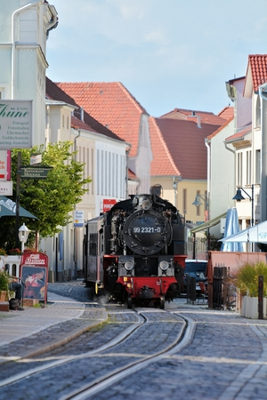 narrow gauge railroad: BAD DOBERAN, GERMANY - AUGUST 24, 2014: The steam train Molli fully loaded with tourists on its way through the streets of Bad Doberan