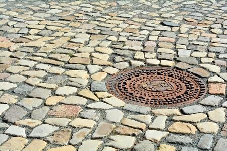 Schachtabdeckung und Kopfsteinpflaster in der Altstadt von Quedlinburg Lizenzfreie Bilder
