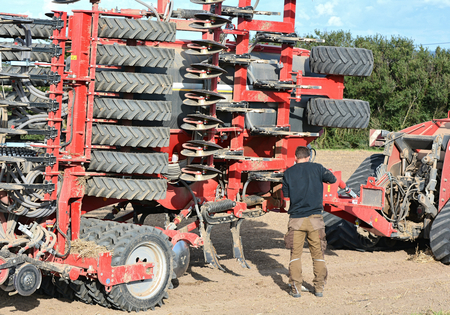 farm field: BASTORF, GERMANY - AUGUST 26, 2014: a farmer during the repair of a machine on the field