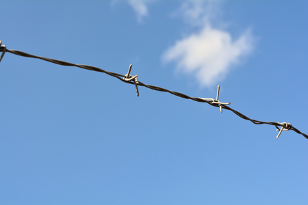 barbed wire on the fence in front of a private property photo