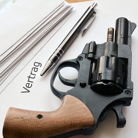dubious: a revolver and a dubious contract is based on a desk in the office