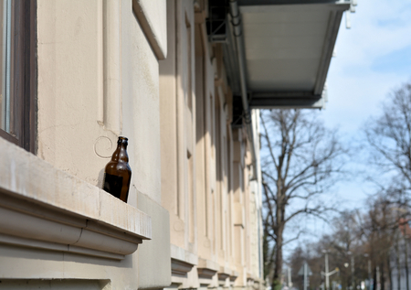 beer after work: beer bottle on the window of a house