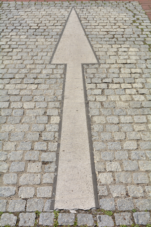 carriageway: Arrow on a road with cobblestones