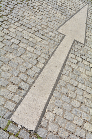 ways to go: Arrow on a road with cobblestones