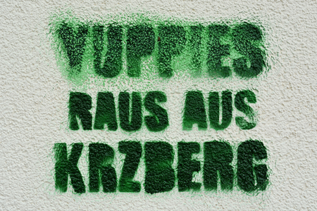 yuppie: protest against yuppies on a house wall in Berlin Stock Photo