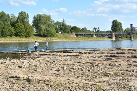 riverbed: Magdeburg, Germany - August 1, 2015: Walkers in the dry riverbed of the Elbe near Magdeburg