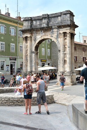 sightseers: PULA, CROATIA - JULY 13, 2015: Tourists in old town of Pula on the Arch of the Sergii