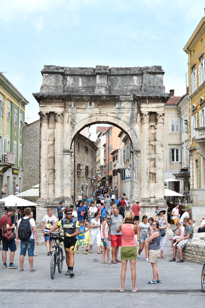 sightseers: PULA, CROATIA - JULY 13, 2015: Tourists at the Arch of Sergi in the old town of Pula in Croatia