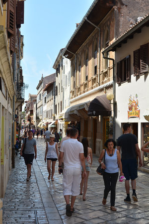 sightseers: POREC, CROATIA - JULY 16, 2015: Tourists in the old town of Porec in Croatia