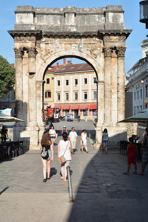 sightseers: PULA, CROATIA - JULY 18, 2015: Tourists at Arch of the Sergii in the old town of Pula in Croatia