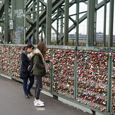 inseparable: COLOGNE, GERMANY - OCTOBER 21, 2015: Padlocks and tourists on the Hohenzollern Bridge in Cologne Editorial