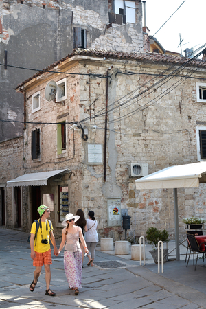 sightseers: PULA, CROATIA - JULY 18, 2015: Tourists When visiting narrow streets in the historic city of Pula in Croatia Editorial
