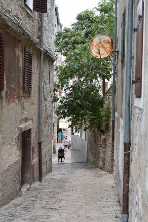 sightseers: PULA, CROATIA - JULY 13, 2015: Tourists When visiting narrow streets in the historic city of Pula in Croatia