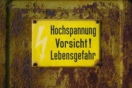 """etiqueta de advertencia amarilla hizo dice """"peligro mortal Precaución alta tensión"""" Foto de archivo"""