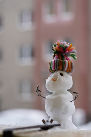 Snowman in winter on a balcony railing Stock Photo