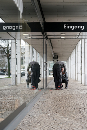 reorganization: HANNOVER, GERMANY - FEBRUARY 01, 2016: two craftsmen during the repair of a entrance door in Hannover Editorial
