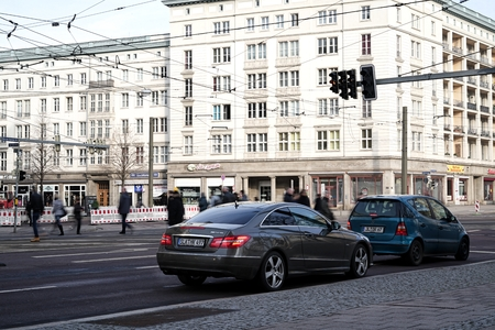 MAGDEBURG, GERMANY - FEBRUARY 19, 2016: intersection with pedestrians and cars at a traffic light in downtown Magdeburg