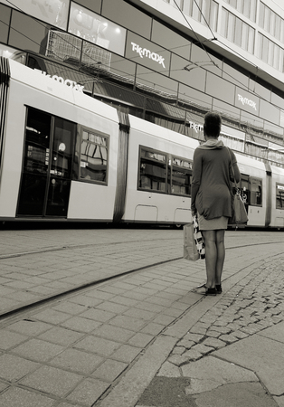 tramline: BERLIN, GERMANY - MAY 9, 2016: young woman waiting on the roadside at Alexanderplatz in Berlin and lets a tram passing Editorial