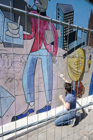 eyesore: BERLIN, GERMANY - MAY 10, 2016: at female artist in the restoration and removal of smearings on the East Side Gallery in Berlin ..