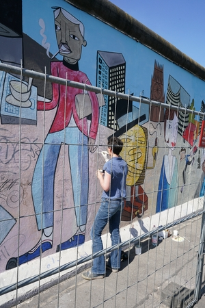 BERLIN, GERMANY - MAY 10, 2016: at female artist in the restoration and removal of smearings on the East Side Gallery in Berlin ..