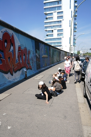 BERLIN, GERMANY - MAY 10, 2016: A school class from Berlin during drawing lesson in front of the East Side Gallery in Berlin