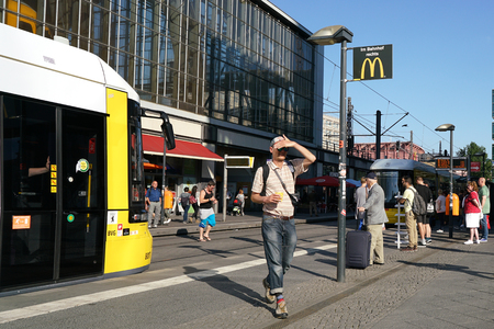 tourists stop: BERLIN, GERMANY  MAY 9, 2016: Tourists and residents at a tram stop at Alexanderplatz in Berlin city center
