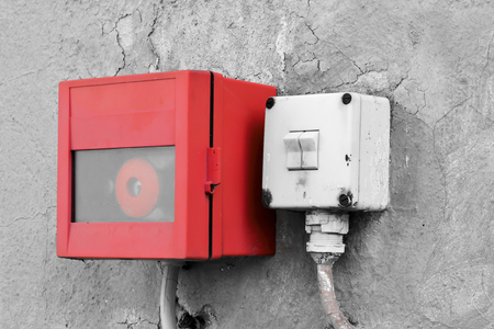 deprecated: emergency switch and light switch on the wall of a factory building